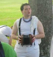 a white person with short dark hair, wearing white pants and a white shirt with black suspenders. Zie is singing and playing a concertina