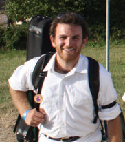 a white man with brown hair and a red beard. he is wearing white pants and a white shirt with black suspenders, looking at the camera and smiling