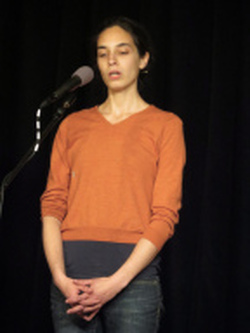 a white woman with dark hair wearing an orange sweater and jeans singing into a microphone