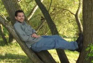 a white man with dark hair and a beard, sitting stretched out in a spreading tree