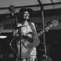 a black and white image of a woman with dark tan skin, dark hair, and glasses. She is wearing a wide-brim hat and overalls, standing on stage smiling and holding a large acoustic guitar