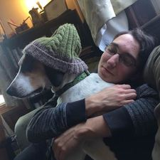 a young white person with glasses and dark hair, hugging a grey dog with a green knit hat on its head
