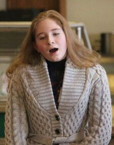 a young white woman with long blond hair singing, wearing a cream cable knit sweater